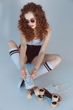 High angle view of hipster girl in sunglasses wearing roller skates sitting. Isolated on grey Royalty Free Stock Images