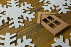High angle view of house with snow flake decoration. On wooden table Royalty Free Stock Photo