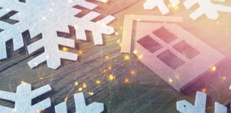 High angle view of house with snow flake decoration. On wooden table Royalty Free Stock Photography