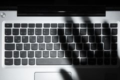 Shadow Of Person`s Hand Falling On Laptop Keypad. High Angle View Of Human Hand`s Shadow Falling On Laptop Keypad royalty free stock images