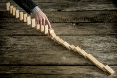 High angle view image of a businessman stopping domino effect Royalty Free Stock Photography