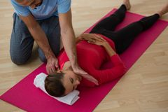 High angle view of instructor guiding student in exercising. At yoga studio Royalty Free Stock Photo
