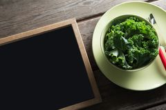 High angle view of kale in bowl on plate by blackboard royalty free stock images