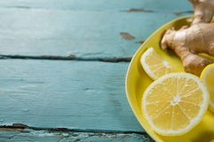 Lemon slices and ginger in plate. High angle view of lemon and ginger in plate on textured wooden table Royalty Free Stock Photo
