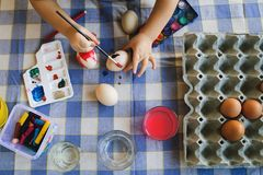 High angle View on little boy painting Easter Eggs at home royalty free stock photo