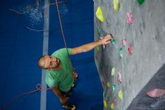 High angle view of male athlete climbing wall in club Royalty Free Stock Images
