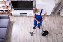 Janitor Cleaning Floor With Vacuum Cleaner. High Angle View Of A Male Janitor Cleaning Floor With Vacuum Cleaner royalty free stock photography