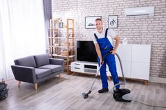 Janitor Cleaning Floor With Vacuum Cleaner. High Angle View Of A Male Janitor Cleaning Floor With Vacuum Cleaner royalty free stock photo