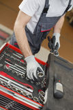 High angle view of male mechanic arranging tools in drawer at car repair shop Stock Image