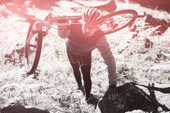 High angle view of male mountain biker carrying bicycle in forest Royalty Free Stock Photo