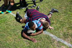 High angle view of man chasing ball while playing rugby. High angle view of men chasing ball while playing rugby on grassy field stock image