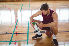 High angle view of man using mobile phone while sitting on basketball Stock Images