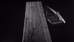 High angle view of man and woman walking on dock at night stock footage