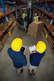 High angle view of manager wearing hard hat and looking workers Stock Image