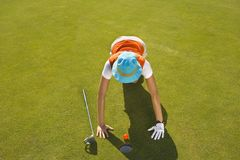 High angle view of a mid adult woman judging a golf ball on a golf course.  Royalty Free Stock Image