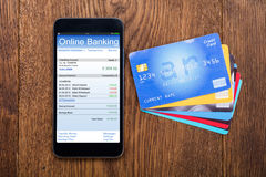 High Angle View Of Mobilephone With Credit Card. High Angle View Of Mobilephone Showing Online Banking With Credit Card On Wooden Desk Royalty Free Stock Images