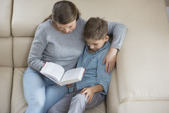 High angle view of mother and son reading book on sofa Stock Image