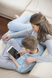 High angle view of mother and son using tablet PC on sofa Royalty Free Stock Image