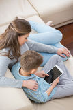 High angle view of mother and son using tablet PC on sofa stock images