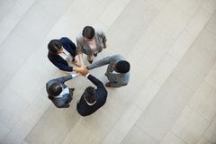Team motivation. High angle view of multi-ethnic business people standing in circle and stacking hands while supporting each other, team motivation concept royalty free stock image