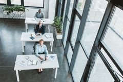 High angle view of multiethnic business people sitting at tables and looking at camera. In modern office royalty free stock photography