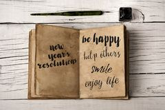 New years resolutions in a yellowish notebook. High angle view of a notepad with some new years resolutions written in it, such as be happy, help others, smile Royalty Free Stock Image