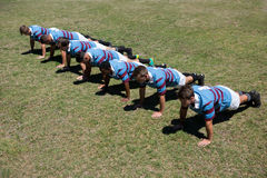 High angle view od players doing push ups ats grassy field. High angle view of players doing push ups at grassy field on sunny day Stock Photography