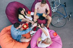 Free High Angle View Of Friends Clinking With Bottles Of Beer And Holding Burgers On Bean Royalty Free Stock Images - 127756759