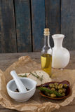 High angle view of olives with oil bottle and bread by spices in mortar pestle on table Royalty Free Stock Images