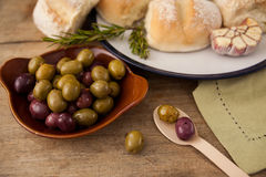 High angle view of olives in plate by bread. On table Royalty Free Stock Image