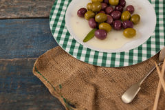High angle view of olives served in plate. On wooden table Royalty Free Stock Photography
