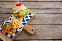 High angle view of onion rings and french fries with burger. On cutting board Stock Photo