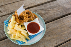 High angle view of onion rings with French fries. Served in plate on table Royalty Free Stock Photography
