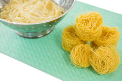 High angle view of pasta in colander with tagliolini on place mat Stock Images
