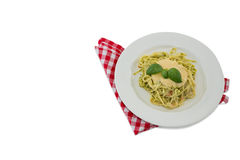 High angle view of pasta served with sauce in plate. On napkin against white background Royalty Free Stock Photos