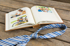 High angle view of photo album by necktie on table. High angle view of photo album by necktie on wooden table Stock Image
