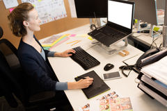 High angle view of photo editor working at desk. In office Stock Image