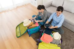 High angle view photo of elegant young sisters. Sitting on living room floor folding clothing and packing luggage suitcase ready to travel Royalty Free Stock Photography