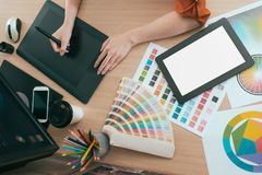 High angle view photo of female graphic designer. Using technology pen working and showing mobile digital tablet pad blank screen in office Royalty Free Stock Photos