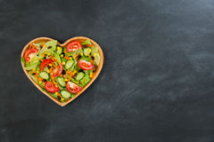 High angle view photo of many vegetable in wooden. Heart shaped plate isolated on black chalkboard with empty design area Royalty Free Stock Photo