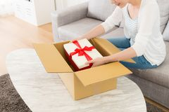 High angle view photo of woman received parcel. High angle view photo of smiling elegant woman received parcel at home and sitting on sofa opened finding having Stock Photo