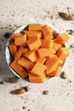 Chopped raw pumpkin in a bowl. High angle view of a pile of chopped raw pumpkin in a pale green bowl placed on a wooden table stock photography