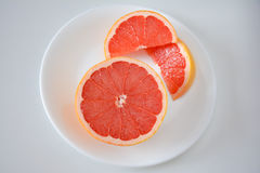 High angle view of Pink grapefruit half and slices. High angle view of a closeup of Pink grapefruit half and slices on a white plate and background Stock Image