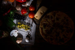 High angle view of pizza with olives, near lie cheese and other vegetables on napkin on wooden table Royalty Free Stock Photo