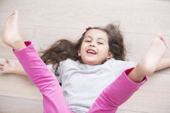 High angle view of playful girl lying on floor with legs raised at home Royalty Free Stock Images