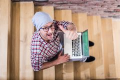 High angle view portrait of fashionable freelancer blogger sitting on stairs and showing thumbs up while holding laptop stock photography