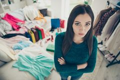 High angle view portrait of nice cute attractive charming pretty candid girl among different clothes difficult choice. Problem question in light white interior stock photos