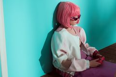 High angle view of pretty girl. In pink wig playing with pink joystick in studio royalty free stock images