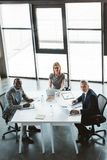 high angle view of professional multiethnic business people smiling at camera while sitting together stock photography