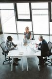 High angle view of professional multiethnic business people working together at table. In modern office royalty free stock photos